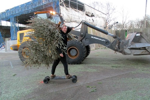 An innovative resident transports his Christmas tree by skateboard