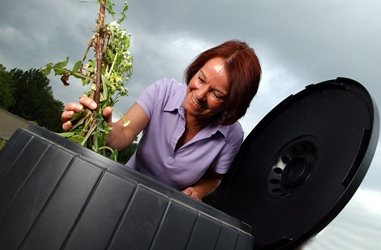 Woman putting garden waste into a compost bin